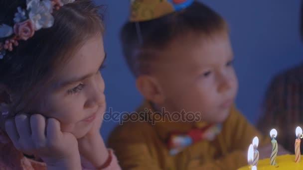 malé děti sedět na červené tabulky s dortem. Šťastné skupina dětí na narozeninovou oslavu.
