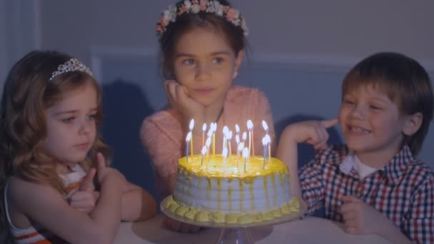 little kids sit at red table with cake. Happy group of children at birthday party.