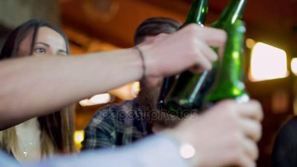 Gli amici ridono, bere birra e cocktail pur avendo un buon tempo insieme in un bar. Slow motion