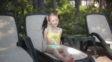 A little girl in a yellow bathing suit is basking in the sun sitting on a sunbed.