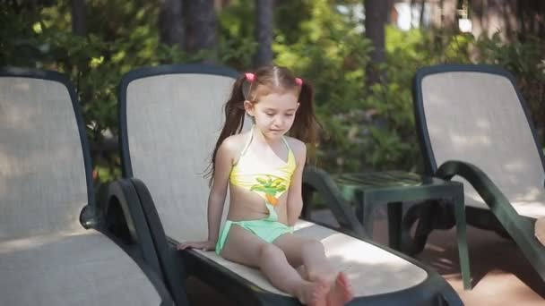 1f5461b1385f3 A little girl in a yellow bathing suit is basking in the sun sitting on a  sunbed.– stock footage