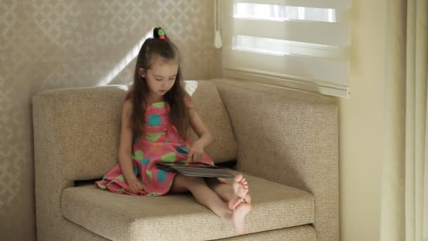 Astounding Little Cute Girl Sitting On Sofa And Playing With Tablet Little Girl In A Beautiful Colored Dress Sits On A Chair By The Window And Uses A Tablet Bralicious Painted Fabric Chair Ideas Braliciousco