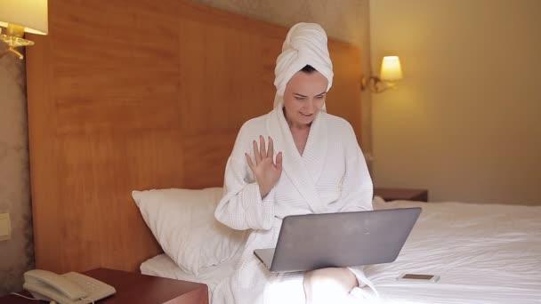 Frau im Bademantel. junge hübsche Frau im Bademantel trinkt Kaffee und schaut ins Fenster, während sie auf dem Bett sitzt