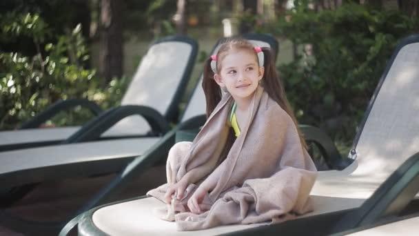 Malá holčička zabalená v ručníku sedí na lehátku u bazénu a vyhřívá na slunci