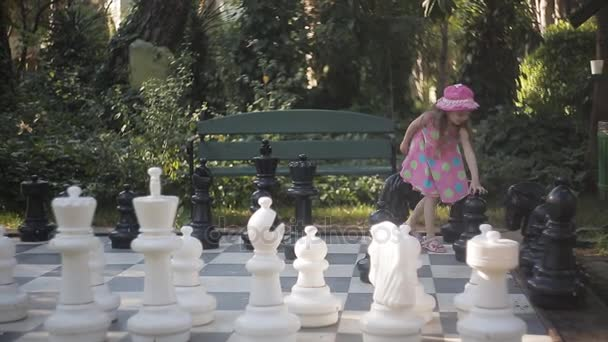 Mom and little daughter play in nature in big chess.