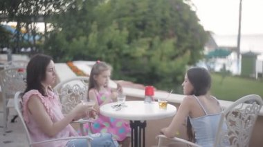 Mom with two daughters in a cafe on vacation to drink juice and talk