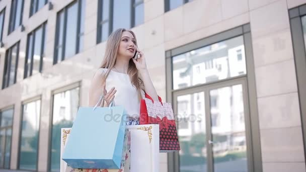 A girl with beautiful multicolored packages after shopping calls her friend and tells about discounts and sales.