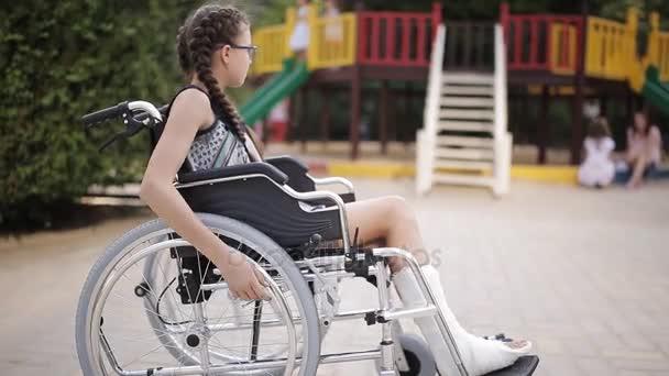 Ein Mädchen sitzt mit gebrochenem Bein im Rollstuhl vor dem Spielplatz.