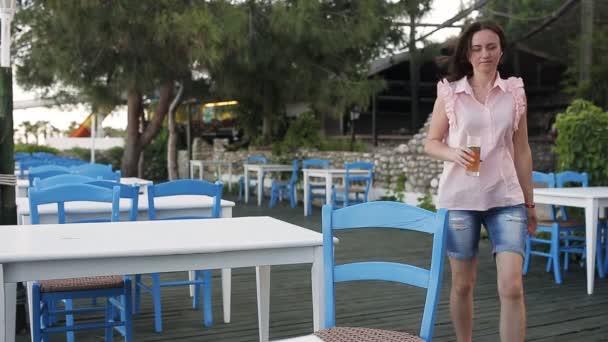 Žena sedí v kavárně s ledová káva s pozadí oblohy a moře