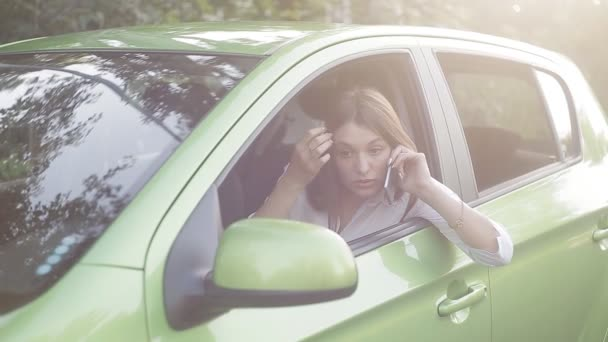 The girl driver communicates by phone in the parking lot and makes notes in her diary