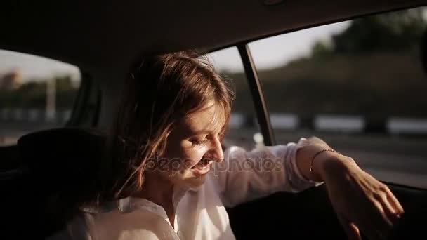 schöne Geschäftsfrau, die im Taxi zu einem wichtigen Meeting fährt und mit Kollegen per Smartphone korrespondiert