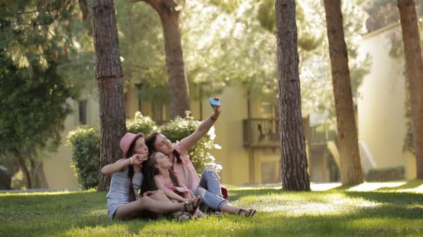 Mom with two daughters in the nature sitting on the grass and making a selfie with a phone