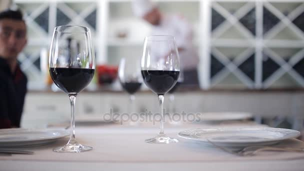 Glasses of wine are on the table of the restaurant, on the background of the cook prepares pasta