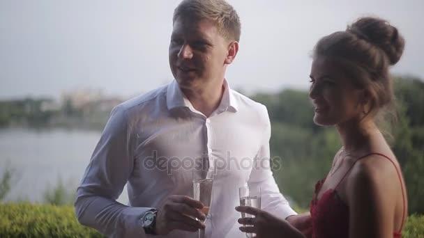 Im Sommercafé gratulieren Freunde einem jungen Paar mit einer Verlobung. Eine Gruppe von Freunden umarmt ein junges Paar in einem Sommerrestaurant