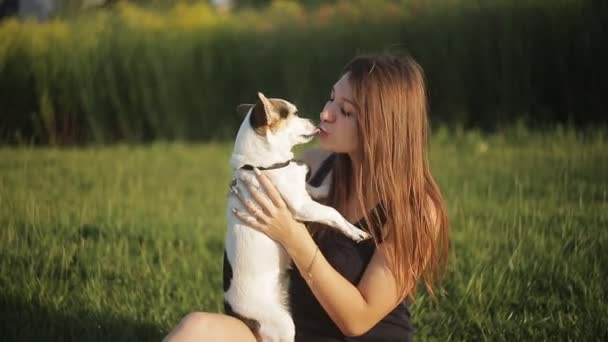 A girl and a dog are kissing in nature She carry on a dog.