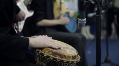 Male hands play a on the African drum. Close-up
