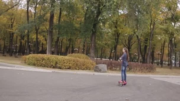 šťastný dospívající dívka na koni elektronické skútr v podzimní park