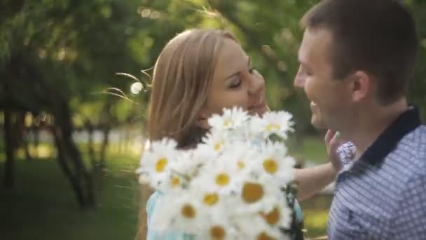Pár v lásce na datum. Ten dává dívka kytici chamomiles