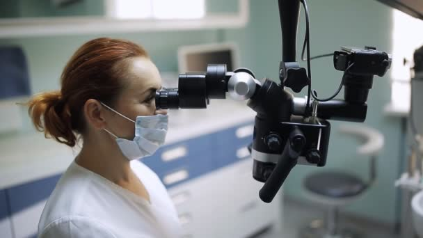 Female dentist with dental tools - microscope, mirror and probe treating patient teeth at dental clinic office. Medicine, dentistry and health care concept. Dental equipment