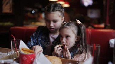 Two little sisters eat French fries in fast food