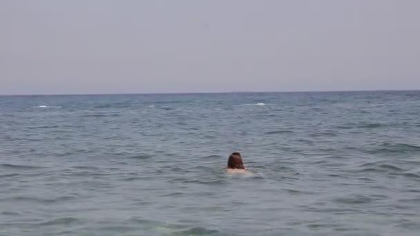 Dívka je koupání v moři