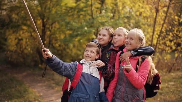 Eine Gruppe schulpflichtiger Kinder mit Rucksäcken auf dem Rücken fotografiert sich mit dem Handy im Park. Glückliche Kinder lachen und machen Selfies