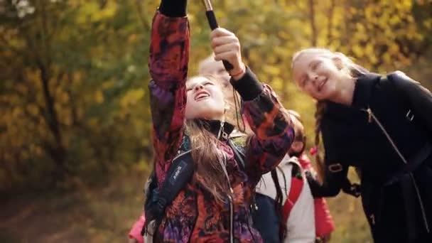 Šťastné děti smát a dělat selfie. Skupina školáků fotit sami v telefonu v parku.