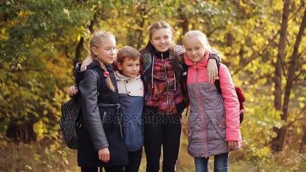 Fröhliche Kinder unterhalten sich und lachen im herbstlichen Park. Herbstpark. Gelbe Blätter