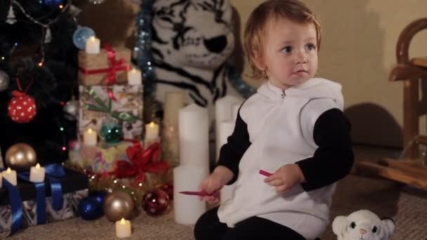 Ein fröhliches kleines Mädchen zeichnet eine Zeichnung für den Weihnachtsmann in der Nähe eines schön geschmückten Weihnachtsbaums. schöner Weihnachtsbaum mit Lichtern. Kerzen neben dem Weihnachtsbaum