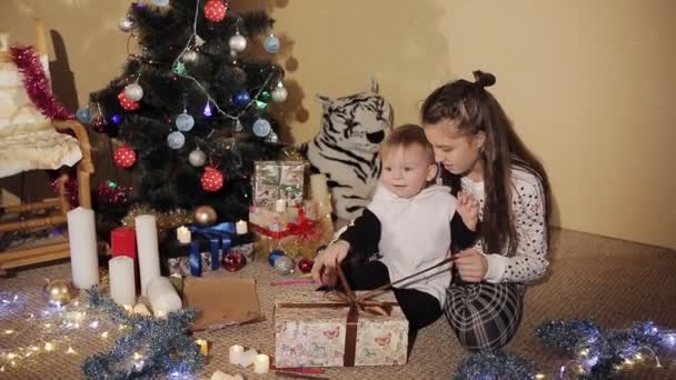 Baby Boy mit Schwester entpacken Silvester-Geschenk-Box in der Nähe ein wunderschön geschmückter Weihnachtsbaum