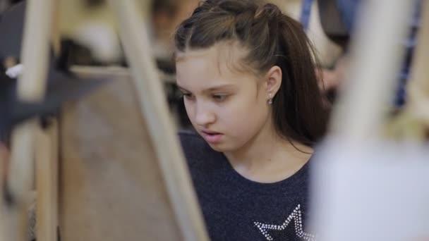 Dívka maluje obraz v dětské studiu výtvarného umění... Některé stojany a plátna na stůl
