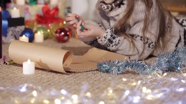Hezká holčička se blíží výkresu pro Santa Claus krásně ozdobený stromeček. Detail. Úchyty holčičku nakreslit obrázek
