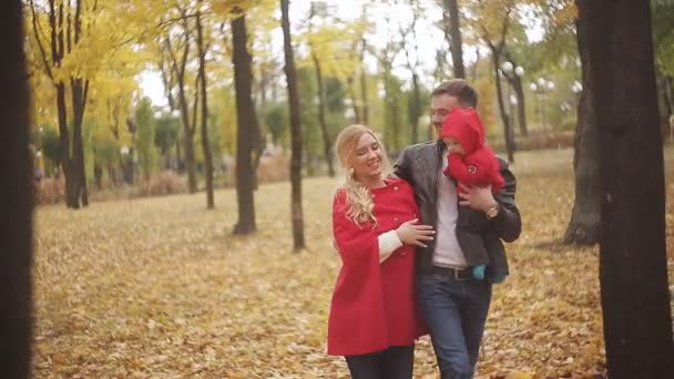 A young family is walking in the park with a baby and enjoying family life