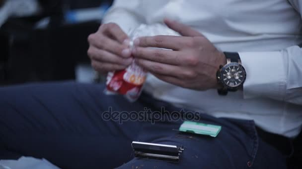 A bearded man makes a cigarette roll-up