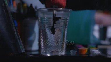 Egy tattooist tintával és egy csésze vízzel a egy tetováló Studió, ban lassú keverés