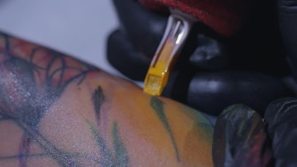 Profesionální tatér provede tetování na ruku mladé dívky ve zpomaleném filmu. Tattoo umělec udělat tetování ve studiu, zblízka