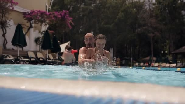 Young dad with a daughter playing and splashing in the pool