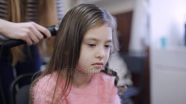 Malá holčička v kadeřnictví. Žena elegán zafixujte lakem. Hypoalergenní sprej na vlasy