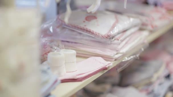 mladá rodina si oblečení pro své nenarozené dítě. Těhotná žena v úložišti. Dětské zboží obchod