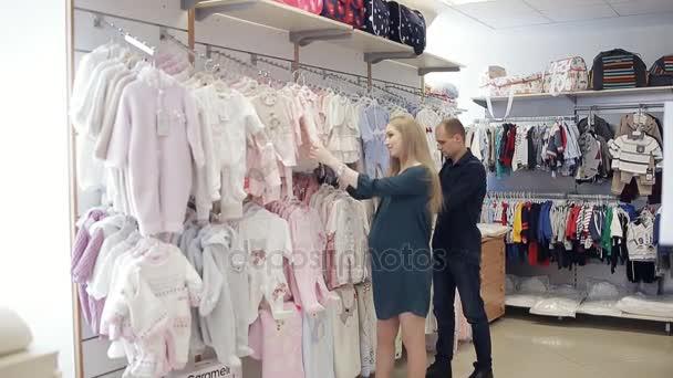 f97d3c64fed07 Femme enceinte heureuse avec son mari dans un magasin de vêtements pour  enfants choisir des vêtements pour le bébé– séquence vidéo