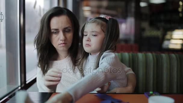 madre lenitivo e che abbraccia neonata gridante. Bella giovane madre calma figlia grida