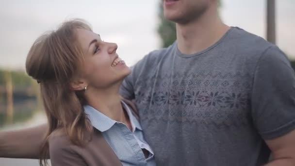 Verliebte bei einem Date am Fluss vor dem Hintergrund der Stadt. ein Kerl umarmt ein glückliches Mädchen