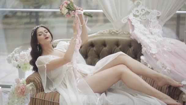 Mladá dívka v negližé a spodních kalhotkách leží na gauči a obdivuje kytici. budoár oblékání nevěsty