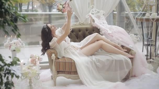 Svatební den nevěsty. Dívka ve spodním prádle a negližé, ležící na pohovce, obdivoval její kytici růží
