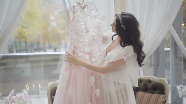 Nevěsta v negližé, stojící u okna a spodních kalhotkách má krásu její svatební šaty