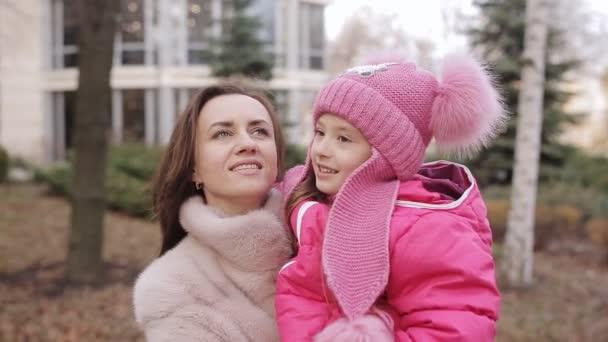 Mutter und Tochter haben Spaß. Baby und Mutter erzählen auf der Straße einen Vers