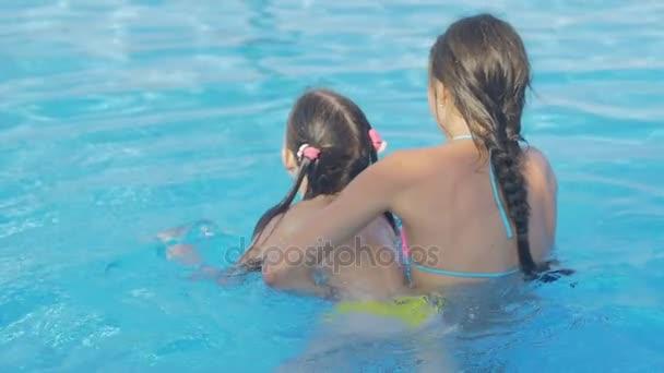 Dívka učí její mladší sestra plavat