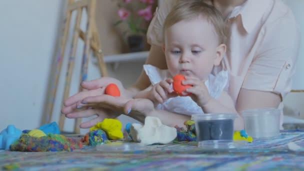 Mladá atraktivní matka s dítětem mladých dělá různé postavy z měkké Plastelíny. Předškolního rozvoje