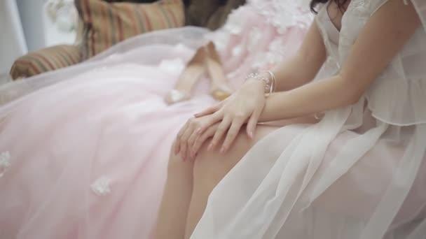 ül a kanapén, egy esküvői ruha, és egy szép csokor virágot közelében átlátszó ruhát visel a gyönyörű boldog menyasszony