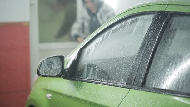Proces mytí auta ve zvláštní místnosti s vodou i pěnou